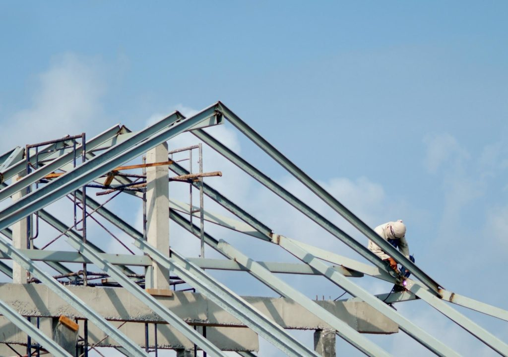 a roofer on the top of the house roof metal brace