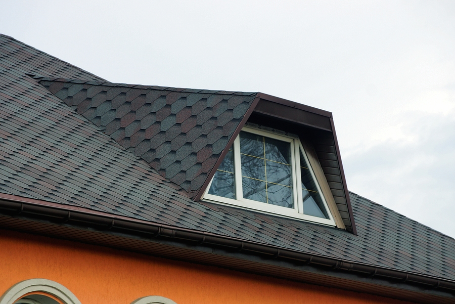 part of the roof of a private house under a tiled roof with a window against the sky