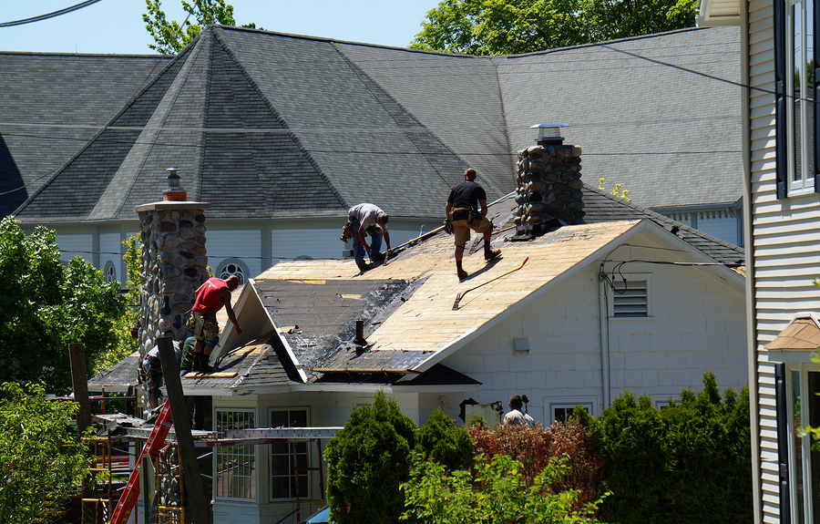 roofers replace the roof on a house