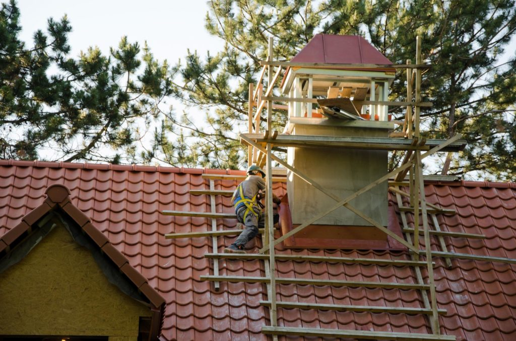 man repairing the house roof