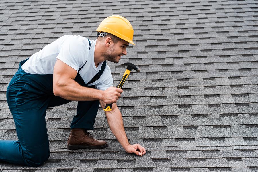 handsome repairman in helmet holding hammer while repairing roof in house
