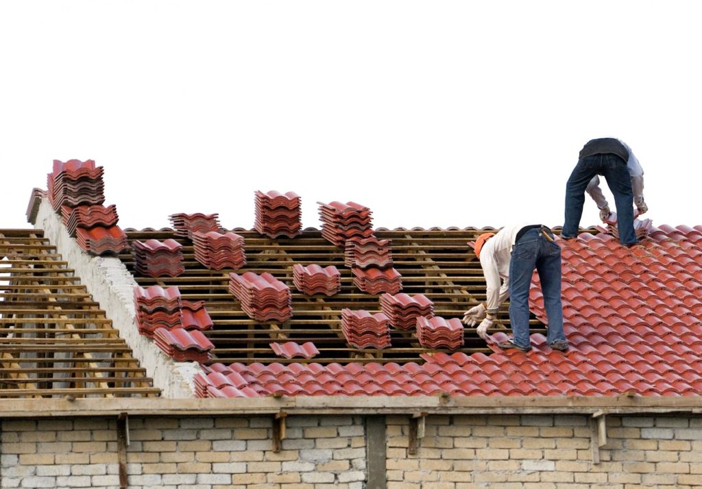 workers are installing house roof tiles